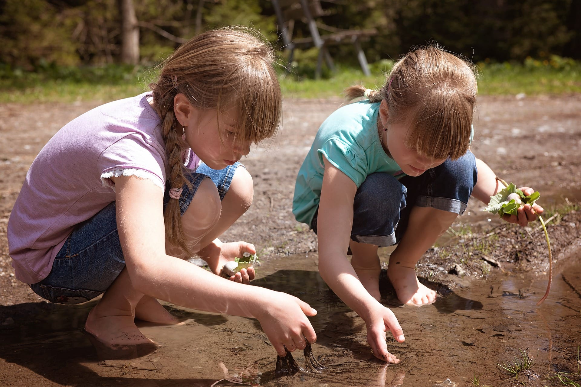 תמונה של שתי בנות משחקות בשלולית