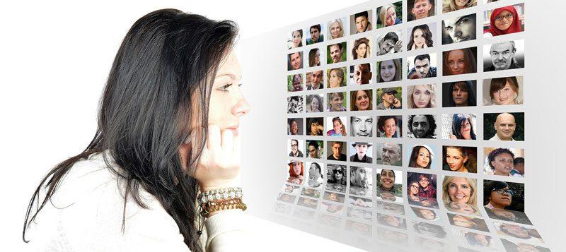 תמונה של אישה מול מסך עם תמונות של אנשים